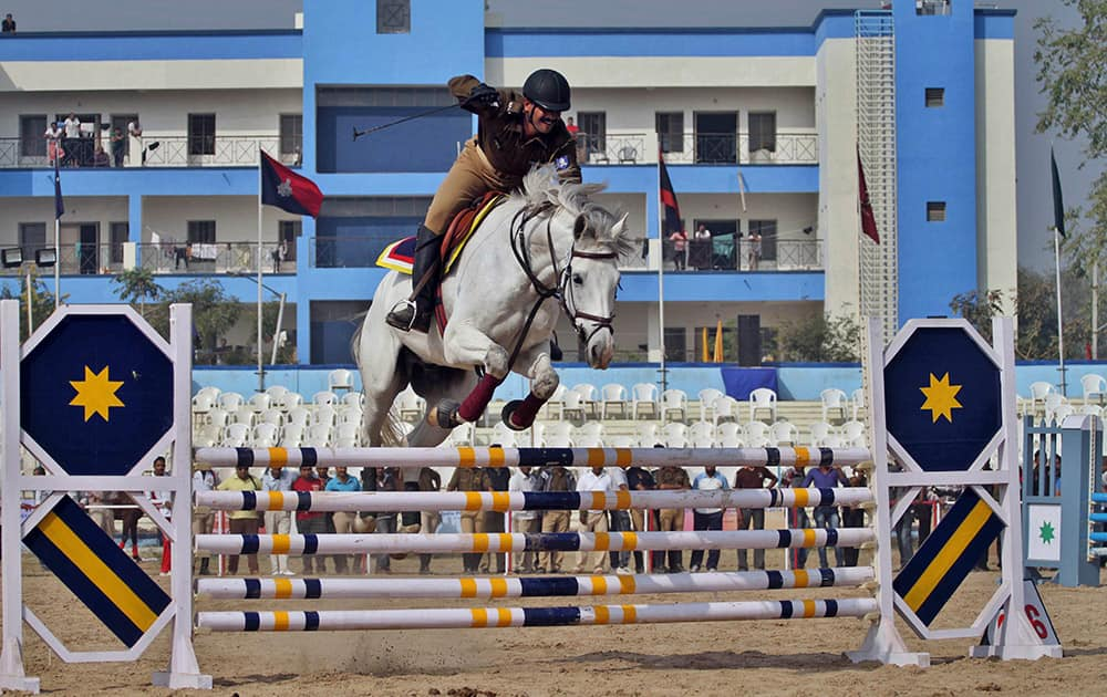 An Indian police horse rider jumps over hurdles during the 32nd annual All India Police Equestrian Meet in Ahmadabad. A total of 18 teams are participating in the weeklong event that began Friday.