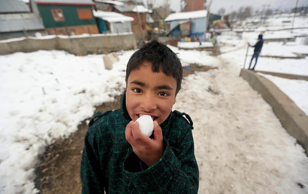 A Kashmiri Muslim boy poses for a photo as he eats snow in Srinagar.