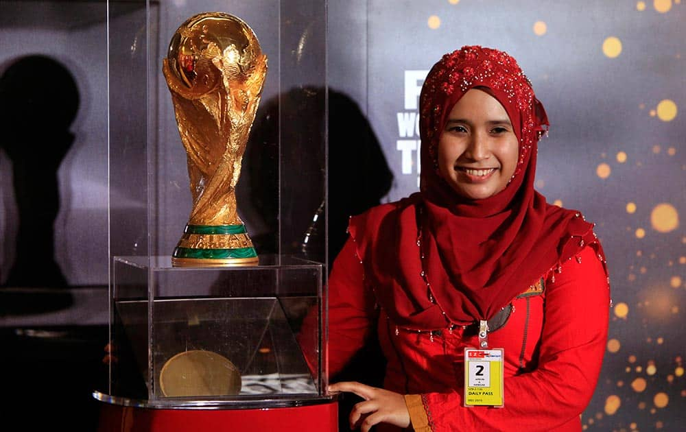 A woman poses with the trophy of the FIFA World Cup in Subang, near Kuala Lumpur, Malaysia.