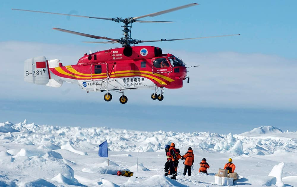 This image provided by Australasian Antarctic Expedition, passengers trapped for more than a week on the icebound Russian research ship MV Akademik Shokalskiy are rescued by a Chinese helicopter.