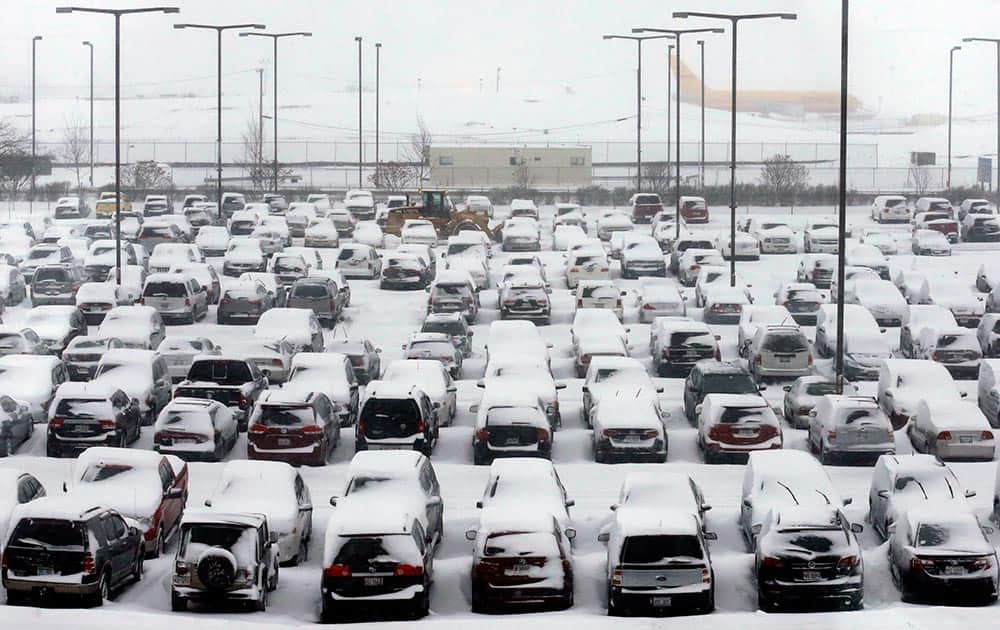 Cars are covered by snow in a parking lot at O`Hare International Airport in Chicago.