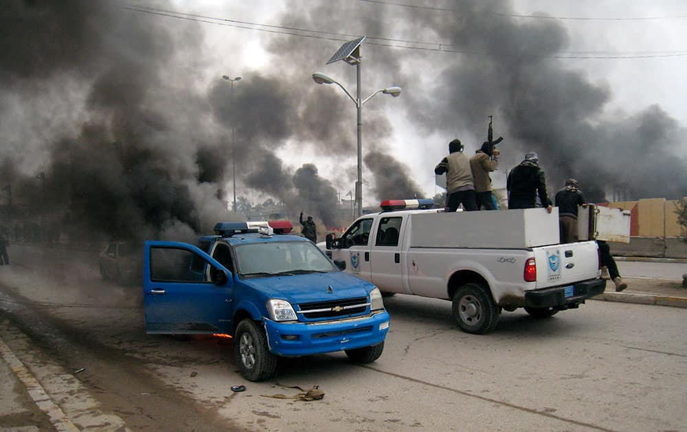 Al-Qaida fighters patrol in a commandeered police truck passing burning police vehicles in front of the main provincial government building, in Fallujah, 40 miles (65 kilometers) west of Baghdad, Iraq.