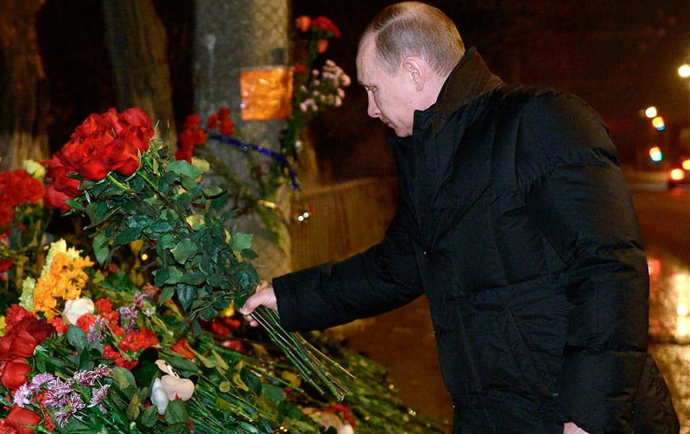 Russian President Vladimir Putin places flowers outside the wreckage of a trolleybus in Volgograd, Russia.