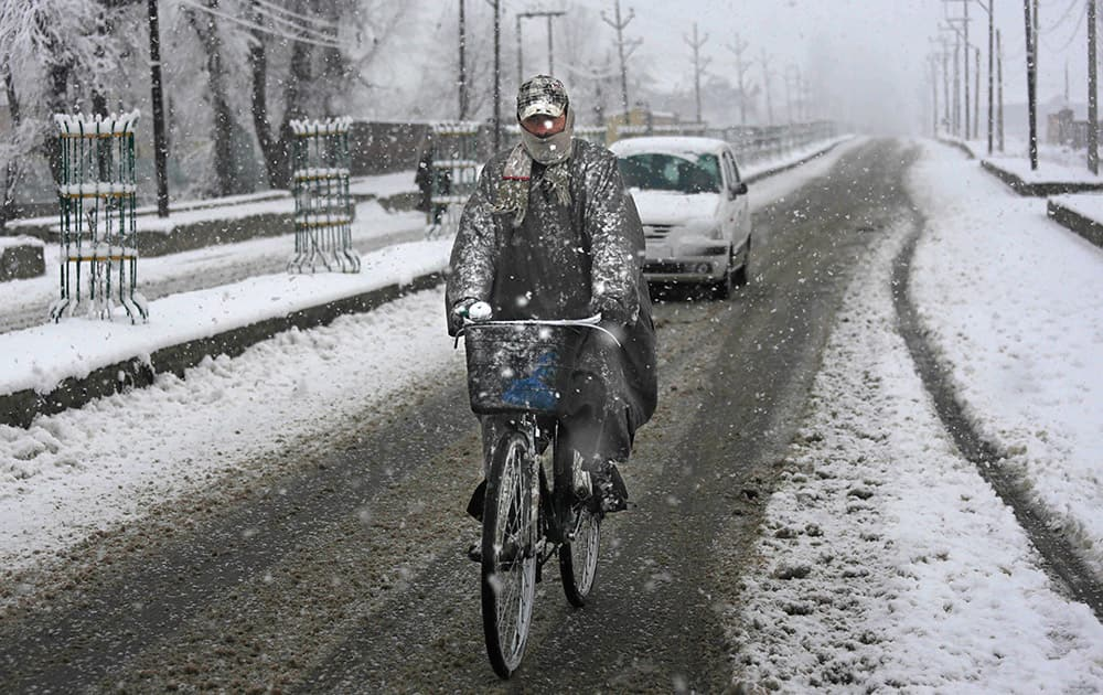 A cyclists rides through snowfall on the outskirts of Srinagar.