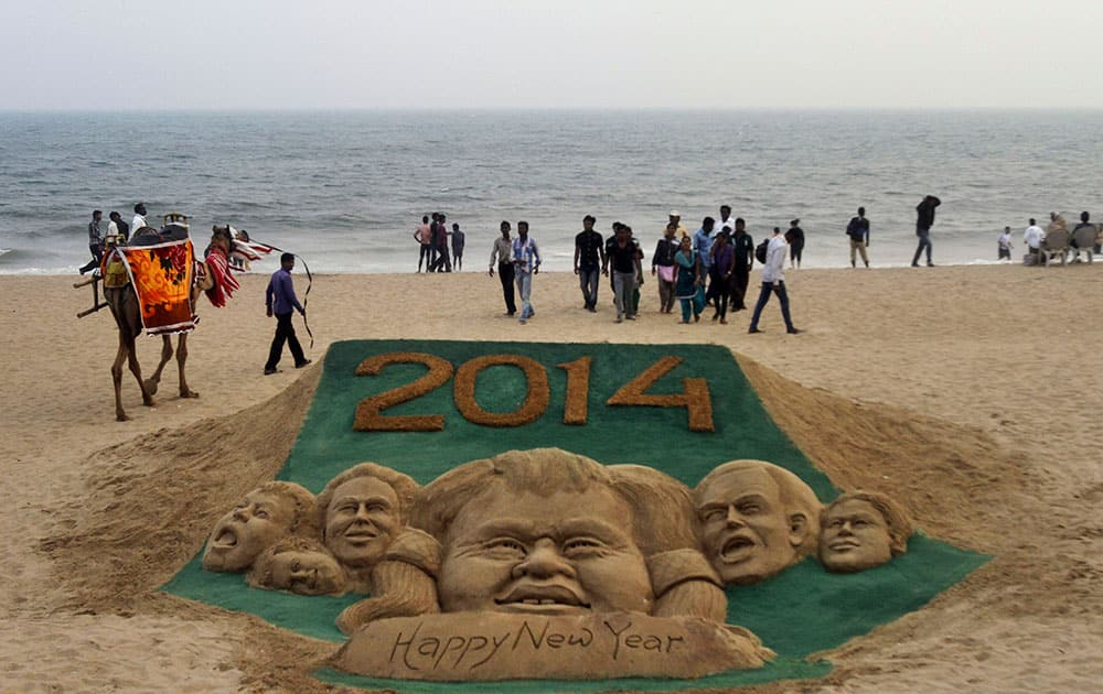 People walk near the sand sculpture to celebrate the new year 2014 created by sand artist Sudarshan Pattnaik at the Puri sea beach, 67 kilometers (42 miles) away from the eastern Indian city of Bhubaneswar, India.