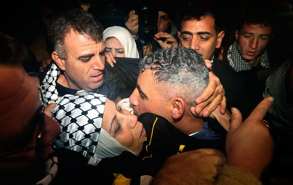 Rami Barbakh, a released Palestinian prisoner, center, is reunited with his mother as he arrives at a checkpoint at the entrance of the northern Gaza town of Beit Hanoun.