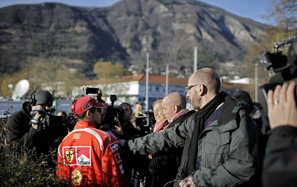 A Scuderia Ferrari fan talks to journalists, in front of the Grenoble hospital, in the French Alps, where former seven-time Formula One champion Michael Schumacher is being treated after sustaining a head injury during a ski accident, in Grenoble, France.