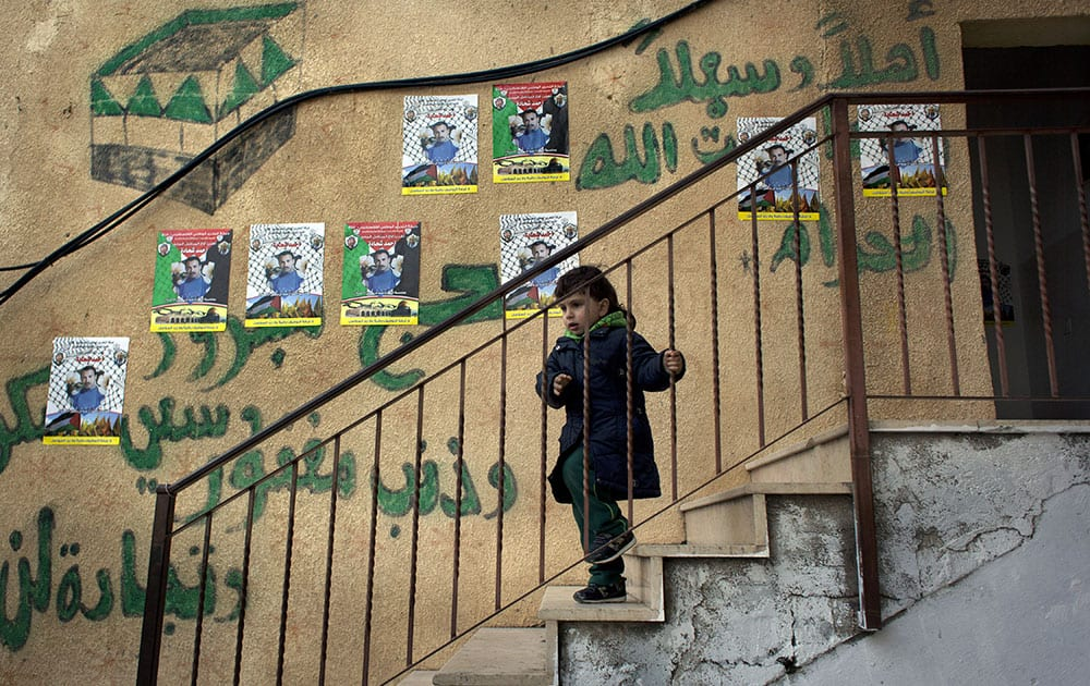 A child walks down the stairs of the family home of Ahmed Shehadeh, one of 26 Palestinian prisoners expected to be released later tonight, next to posters with his picture and Arabic that reads