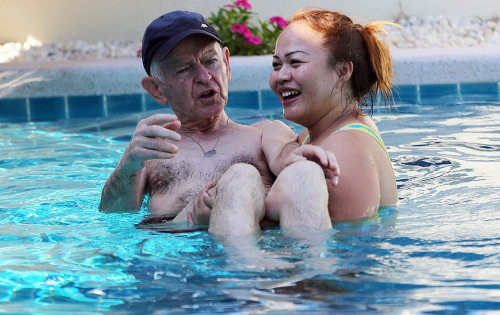 A Thai caretaker, right, carries Gerhard, an Alzheimer patient from Switzerland in a swimming pool at Baan Khamlangchai care center in Chiang Mai province, northern Thailand.
