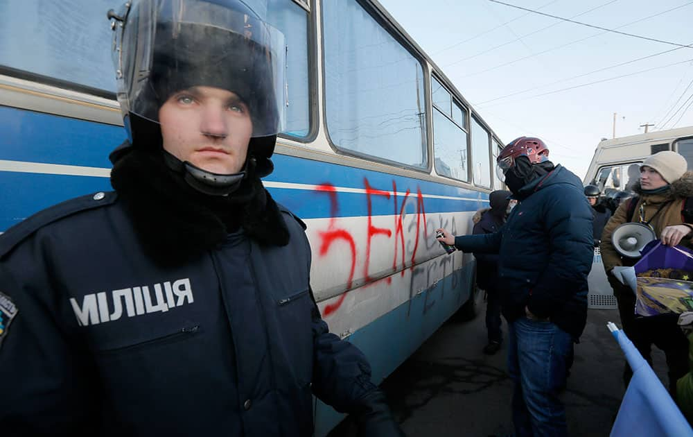 A riot police officer looks on as a pro-European Union activist writes an anti-presidential graffiti on a riot police bus a few hundred meters from Ukrainian President Viktor Yanukovych's country residence of Mezhygirya outside Kiev, Ukraine.
