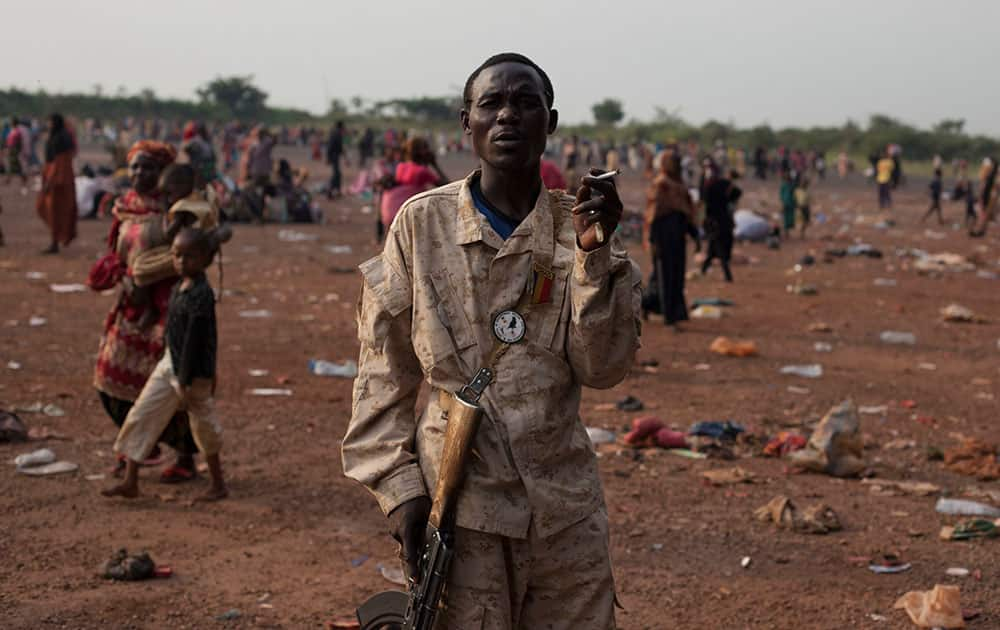 A Chadian soldier, part of an African peacekeeping force, smokes a cigarette as he stands guard over Chadians waiting for evacuation flights, at the airport in Bangui, Central African Republic.