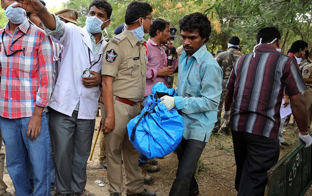 A volunteer carries the remains of a charred body of a passenger near the site of a train accident at Kothacheruvu, about 155 kilometers (96 miles) north of Bangalore.