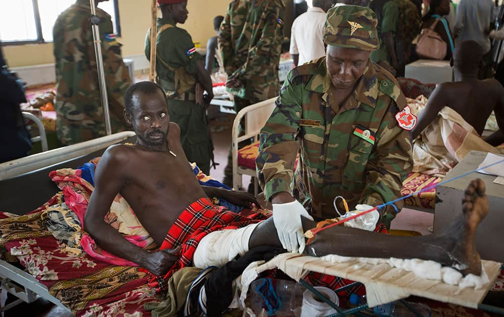 A patient is treated by a military doctor in a ward of mainly soldiers with gunshot wounds, during a visit by current Vice-President James Wani Igga, at the Juba Military Hospital in Juba, South Sudan.