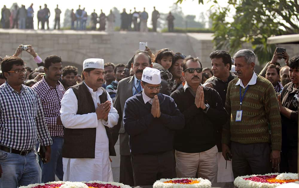 Aam Aadmi Party, or Common Man`s Party, leader Arvind Kejriwal, center, pays respect at the memorial of Mahatma Gandhi after being sworn in as the chief minister of Delhi, in New Delhi.