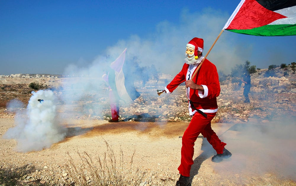 A Palestinian protester wearing a Santa Claus costume runs away from a tear gas canister fired by Israeli troops during a protest against Israel`s separation barrier outside the West Bank village of Bilin, near Ramallah.