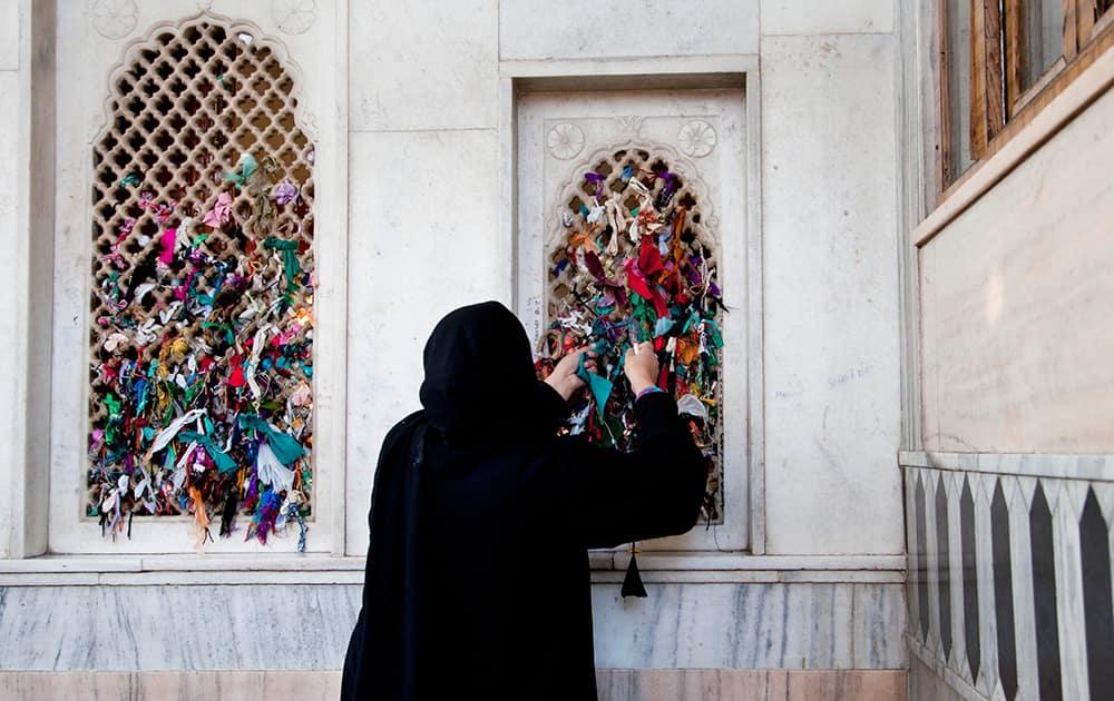 A Kashmiri woman ties a thread on the window of the shrine of Sufi saint Hazrat Sheikh Hamza Makhdoom, commonly known as Sultan-Ul-Arifeen, on the eve of the saint`s Urs, in Srinagar.