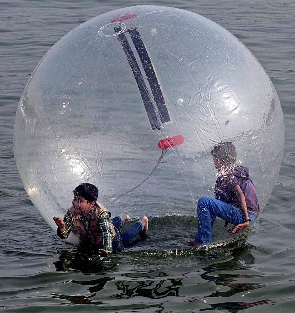 Youths enjoy a ride in floating spheres as tourists throng Kankaria lake in Ahmedabad on Thursday during one week long Kankaria Carnival.