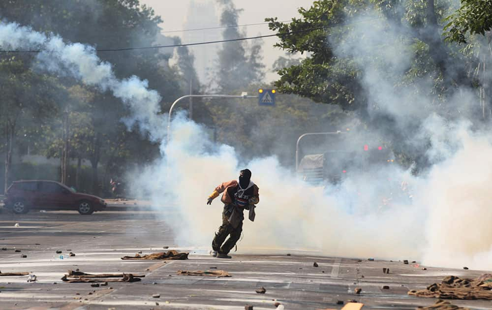 An anti-government protester runs away from tear gas canister fired by riot police near a gymnasium in Bangkok, Thailand.