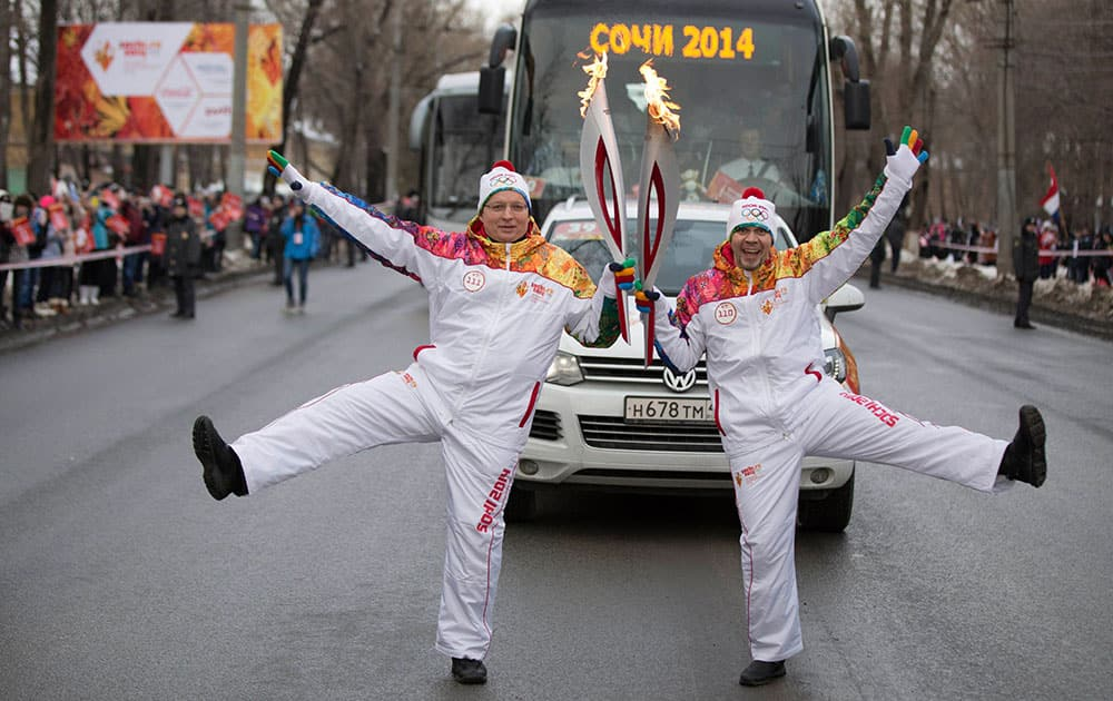 Torch bearers, Andrei Golovanov, left, and Dmitry Ramzanov pose during the Olympic torch relay in Samara on the Volga River, in Russia. The 65,000-kilometer (40,389 mile) Sochi torch relay, which started on Oct. 7, is the longest in Olympic history.