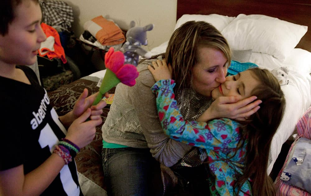 Jill Ghantous, center, kisses her daughter, Briana Ghantous, 6, at the Wingate Hotel,in Grand Blanc Township, Mich. The Ghantous family lost power on Sunday at their home in Swartz Creek due to ice storms that have left about 40,000 people in Genesee County without power. Lacking power at their home, the family opened their Christmas presents Wednesday morning at the hotel.