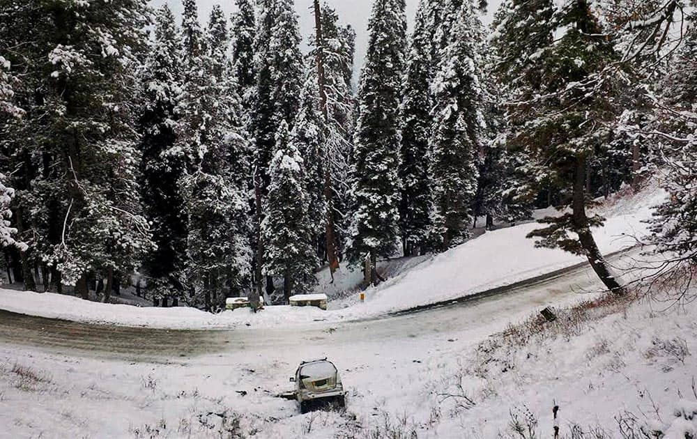 A car stuck in a snow-clad area after snowfall at Gulmarg in Baramulla district.