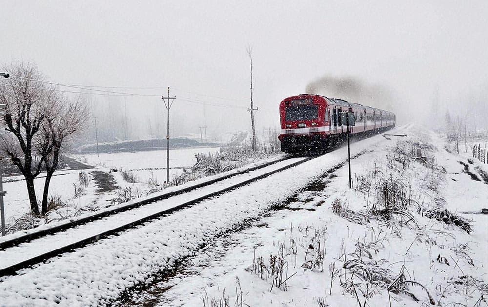 A train runs on Banihal-Baramulla railway track during snowfall in Qazigund.