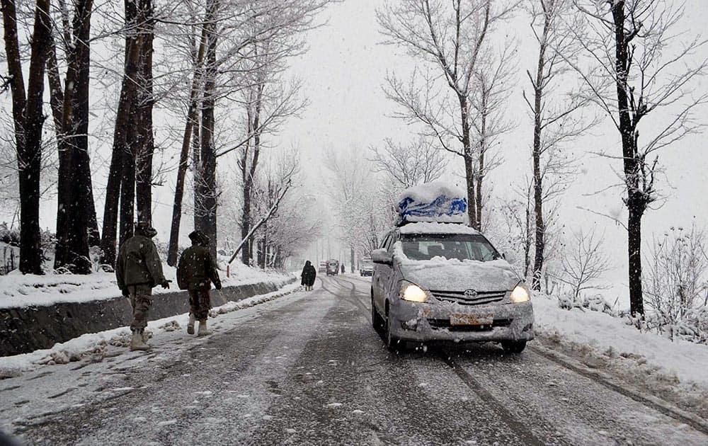 Paramilitary Central Reserve Police Force (CRPF) personnel patrol along the 300-km long Srinagar-Jammu National highway near Qazigund during heavy snowfall.