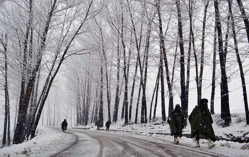 Paramilitary Central Reserve Police Force (CRPF) personnel patrol along the 300-km long Srinagar-Jammu National highway near Qazigund which remained closed for the second consecutive day on Monday for vehicular traffic due to heavy snowfall.