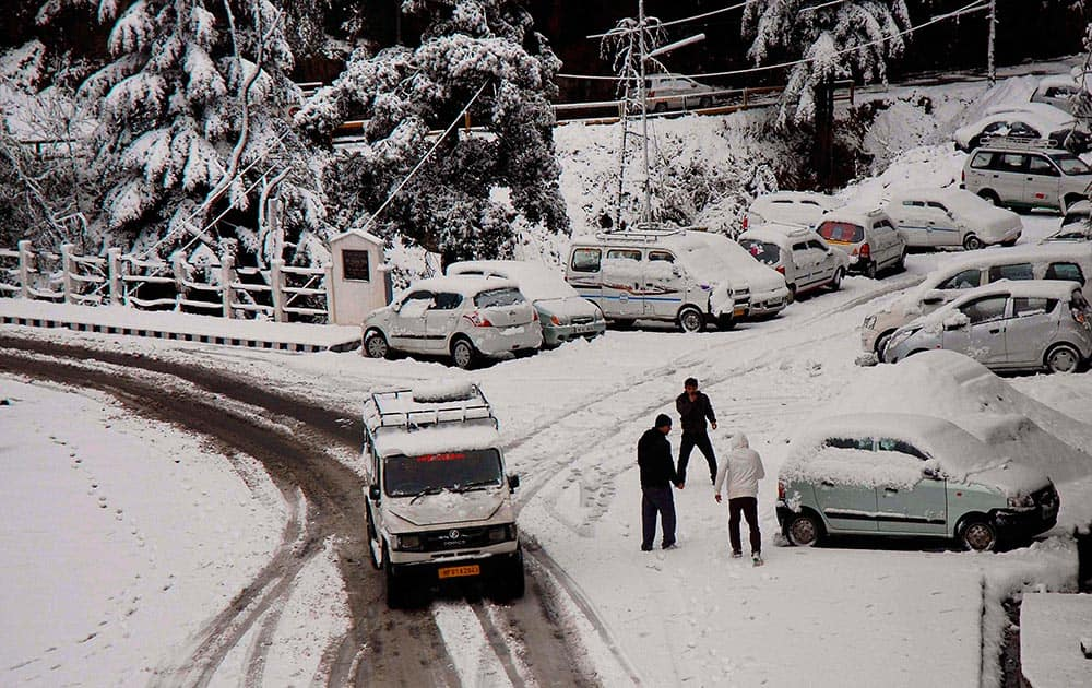 A vehicle moves on snow-covered road after the season`s first snowfall in Shimla.