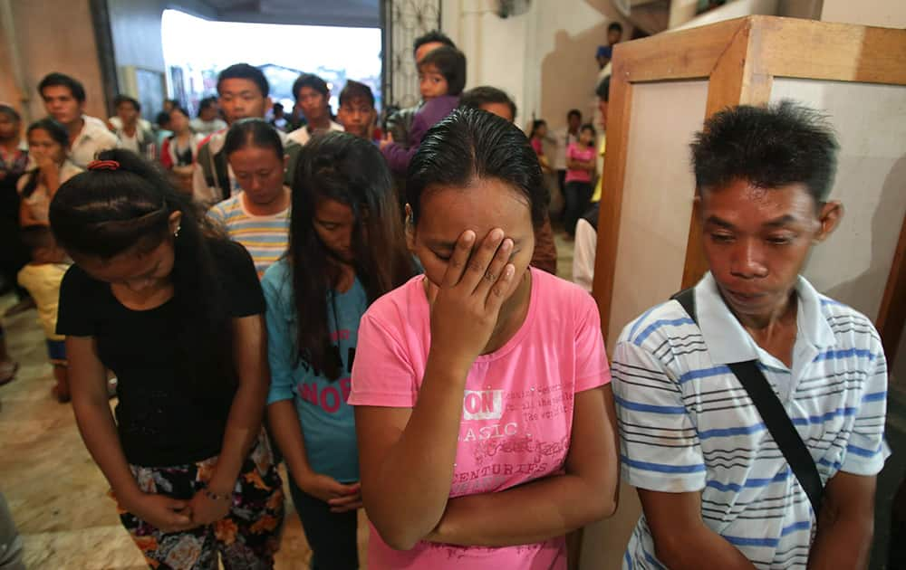 Typhoon survivors pray while attending a dawn Mass in anticipation of Christmas in Tacloban, Philippines.  Many Filipinos attend nine consecutive dawn Masses before Christmas as part of traditional practice in this largely Roman Catholic nation.