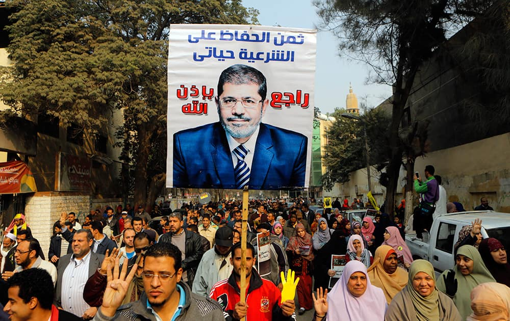 Supporters of Egypt`s ousted President Mohammed Morsi hold his poster as they raise their hands with four fingers which has become a symbol of the Rabaah al-Adawiya mosque, where Morsi supporters had held a sit-in for weeks that was violently dispersed in August, during a protest in Cairo, Egypt.