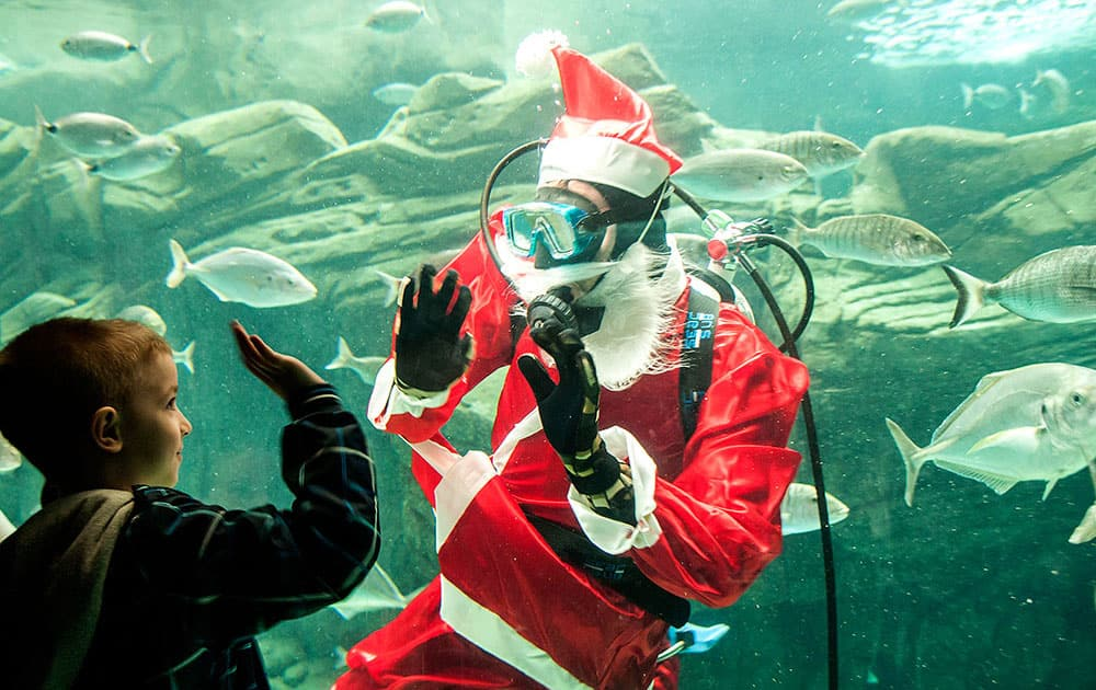A DIVER DRESSED AS SANTA CLAUS WAVES AT A CHILD AT THE CRETA AQUARIUM IN THE CITY OF IRAKLIO, ON THE GREEK ISLAND OF CRETE.