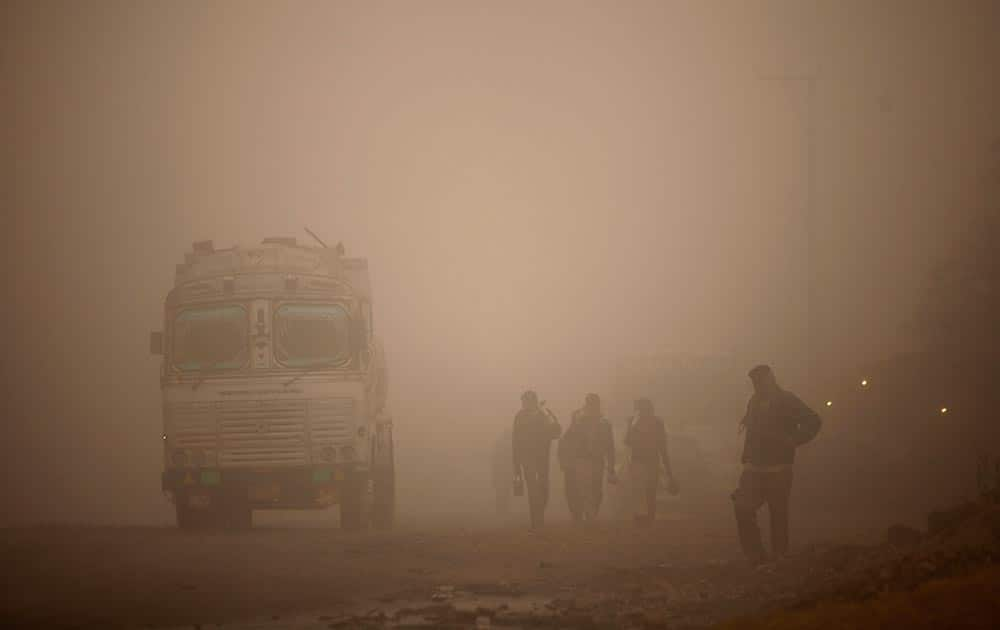 Indian laborers walk to work surrounded by morning fog in Jammu.