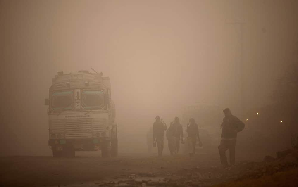 Laborers walk to work surrounded by morning fog in Jammu.