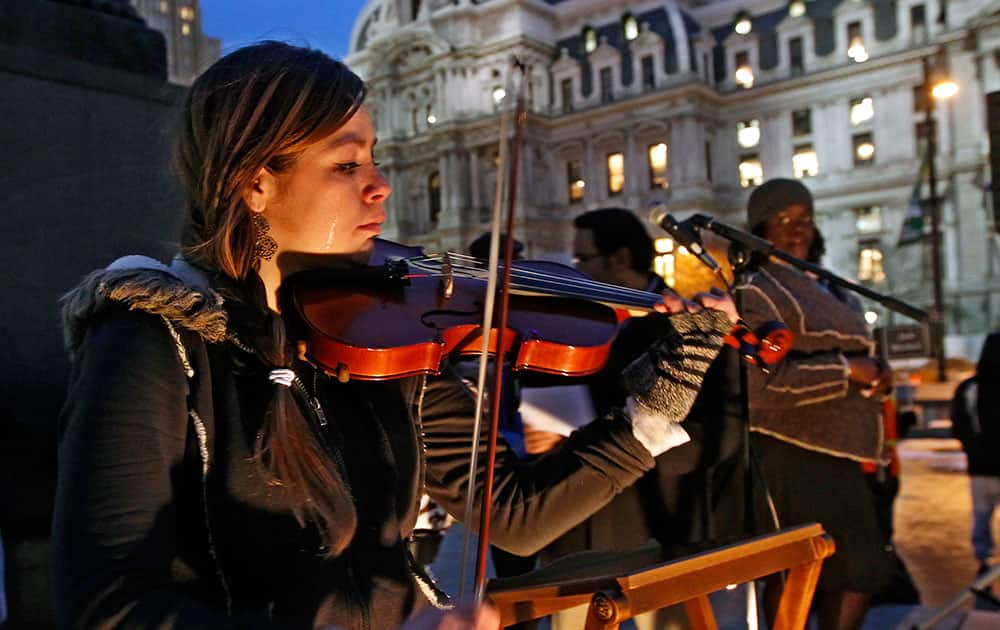 Tears stream down the face of Shandi Beardsley, as she plays her violin while the names of the homeless that have died are read over the public address system to the crowd gathered at Thomas Paine Plaza for the Homeless Memorial Day, in Philadelphia.