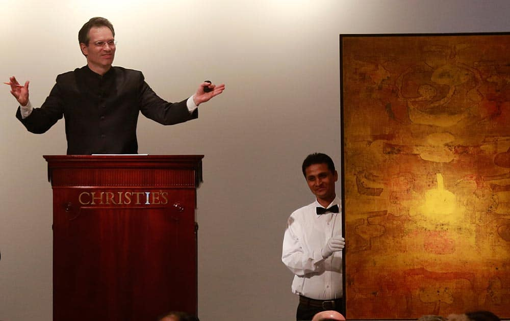 Christie's International Director, Asian Art, Hugo Weihe, left, acts as auctioneer for the painting of Indian artist Vasudeo S. Gaitonde during Christie`s first auction in India in Mumbai.