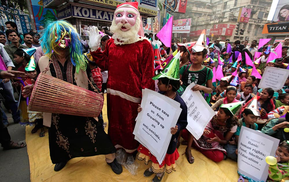 A folk singer performs and a man dressed as Santa Claus waves as underprivileged children wear festive hats and hold placards during a sit-in demonstration demanding basic human rights in Kolkata.