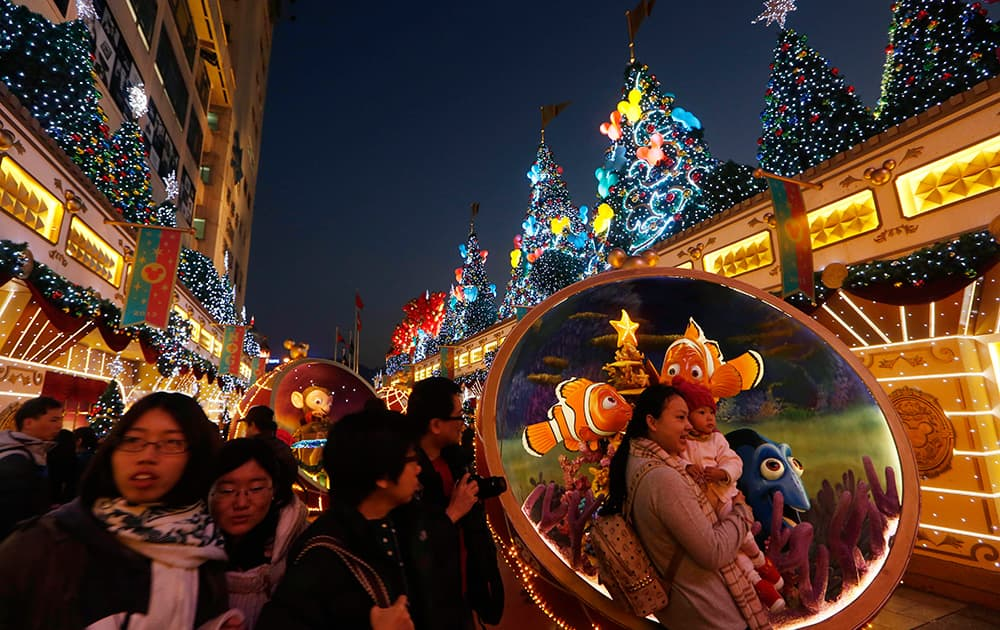Visitors pose for photographs in front of Christmas decorations displayed in celebration of the holiday season at a shopping mall in Hong Kong.