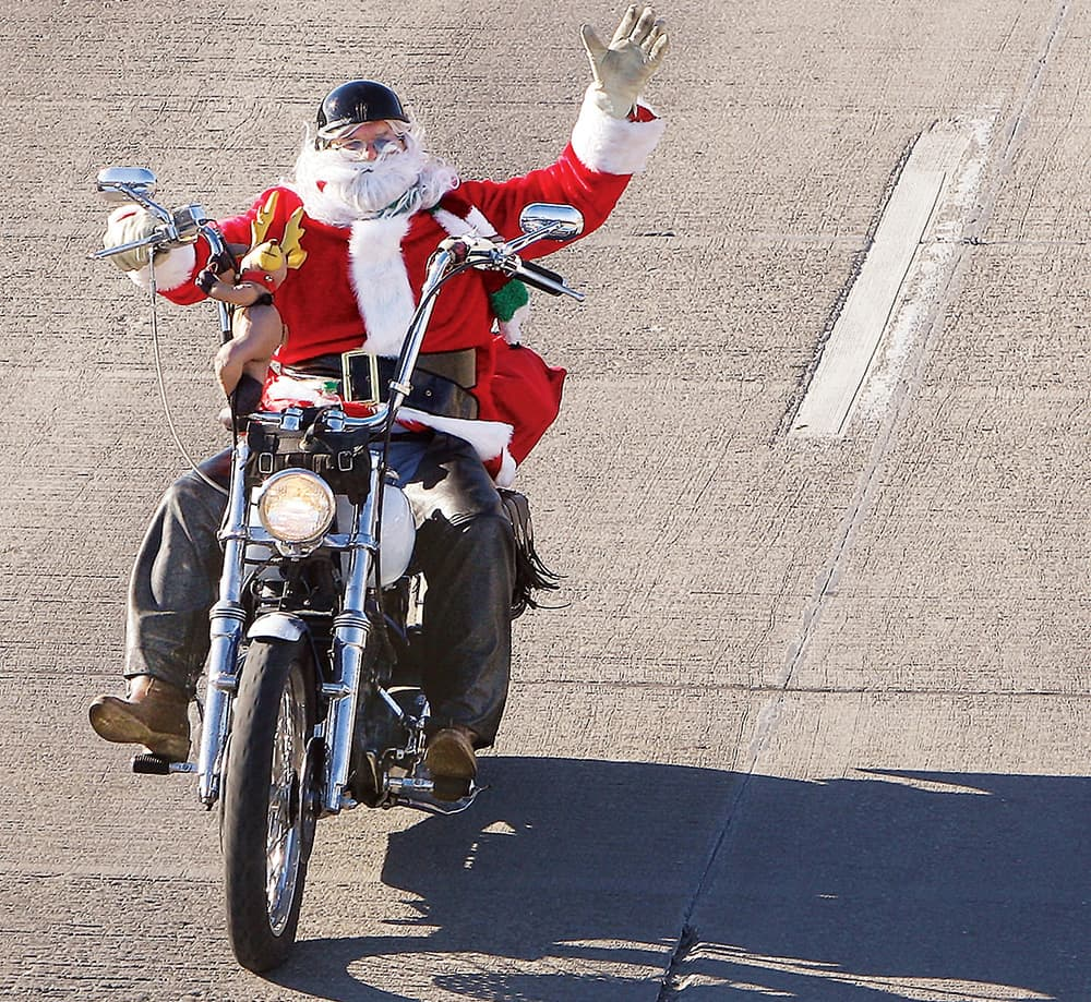 Herman Morgan of Florissant, Mo., takes advantage of the moderation in the weather, to dress up as Santa Claus and go for a ride through Alton, Ill., on his motorcycle.
