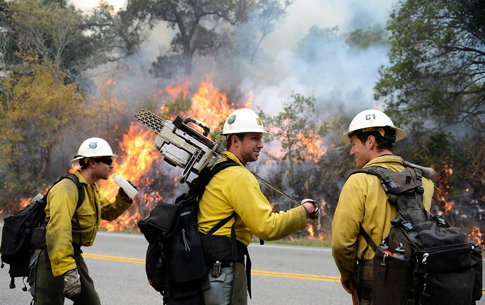 Los Padres National Forest firefighters, from left, Michael Sheppard, Tyson Navarro and Alex Woodhull take a break while lighting a backfire along Highway 1 between Pfeiffer Ridge Road and the Big Sur Station in Big Sur, Calif.