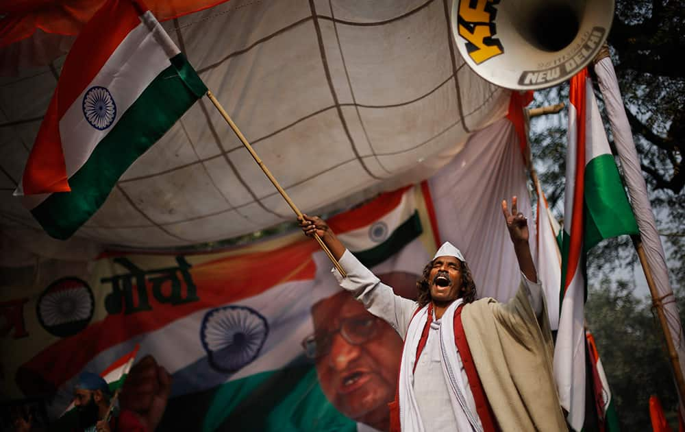 A supporter of social movement leader Anna Hazare waves the national flag as he celebrates the news of passing of a contentious anti-graft bill that empowers an independent ombudsman to investigate and prosecute cases of corruption by politicians and bureaucrats, in New Delhi.