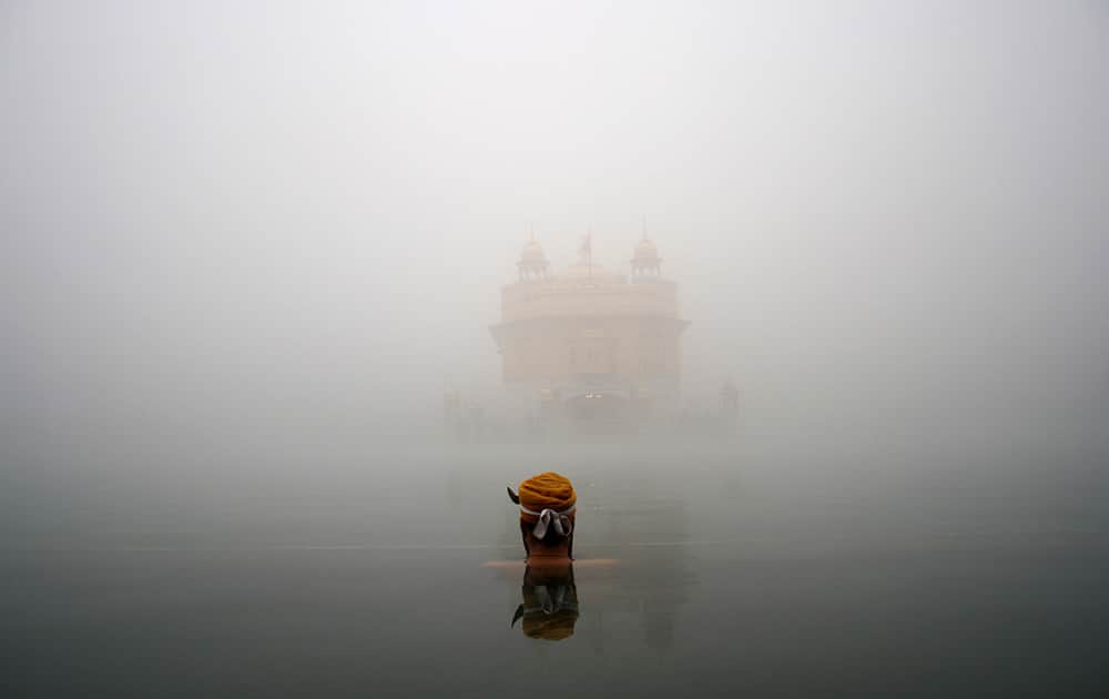 A Sikh devotee takes a holy bath in a sacred pond at the Golden Temple, the holiest Sikh shrine, amidst thick fog in Amritsar.
