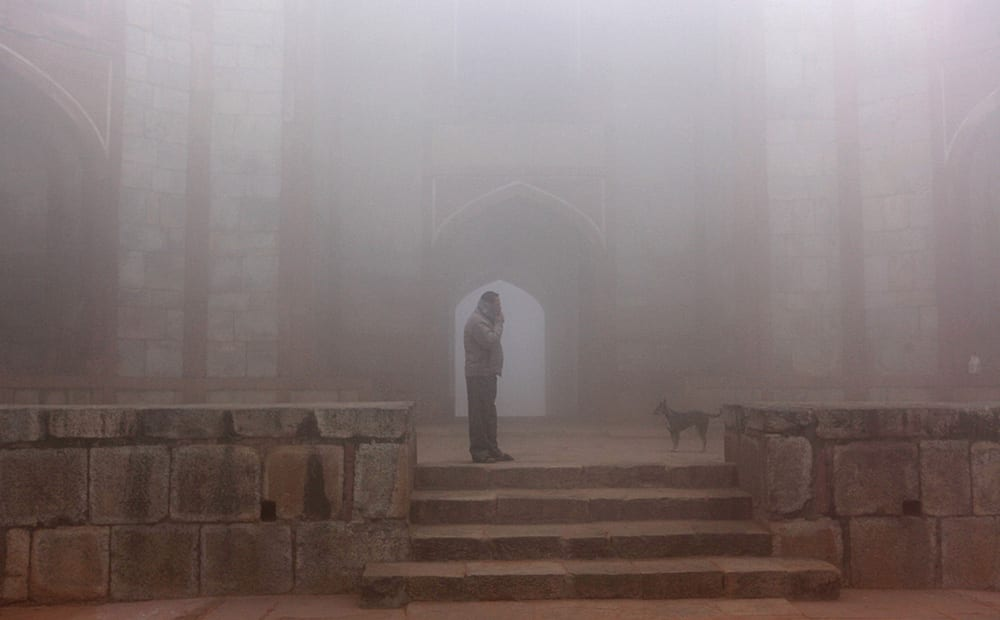 A man smokes a cigarette on a foggy morning in New Delhi.