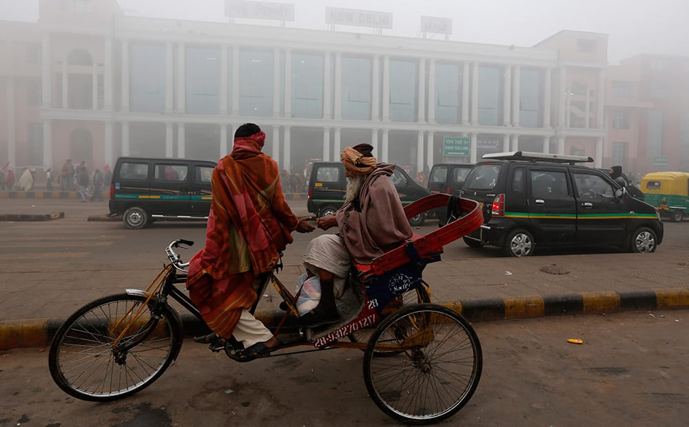 A passenger pays a rickshaw driver outside a railway station surrounded by fog in New Delhi.