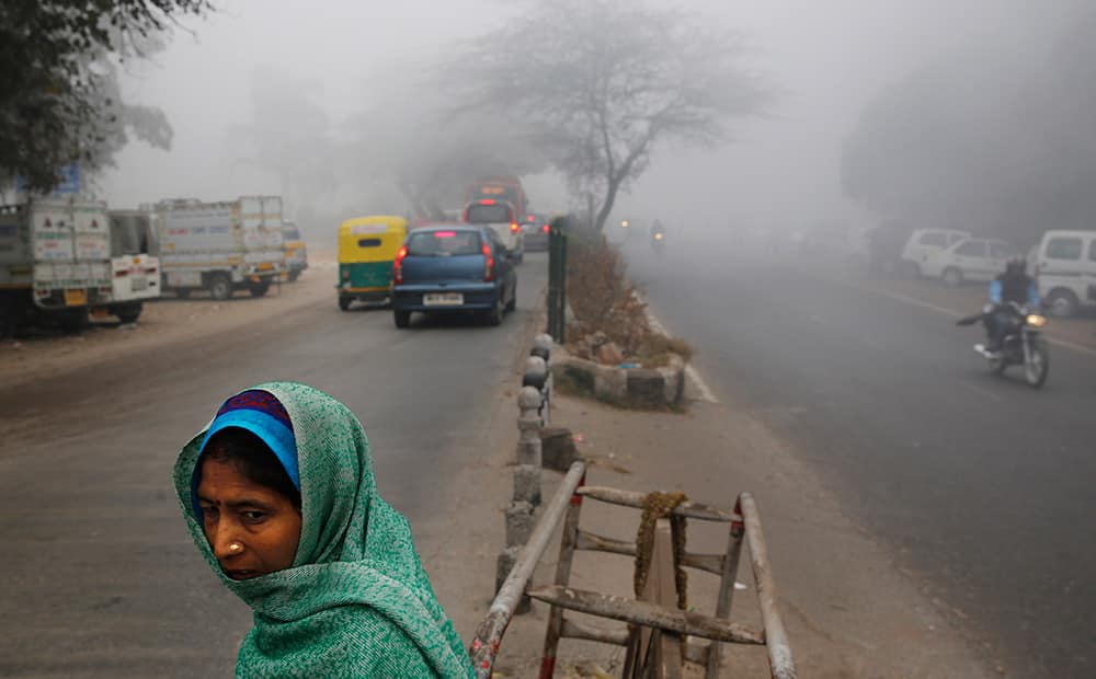 A woman crosses a road surrounded by morning fog in New Delhi.