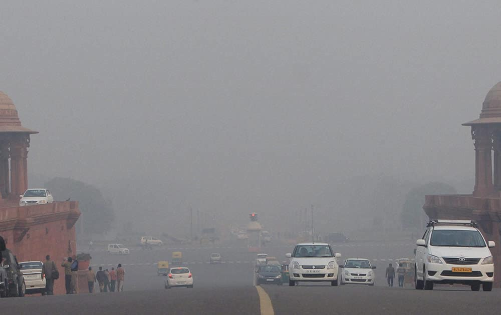 Vehicles plying at Rajpath during a foggy day in New Delhi.