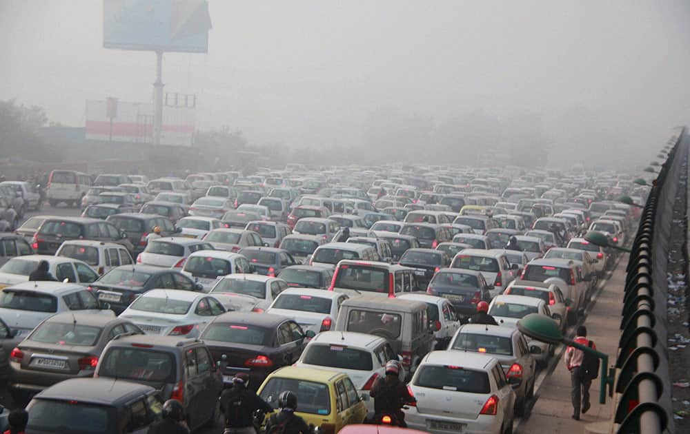 Vehicles stuck in a traffic jam blanketed by a thick fog at Delhi-Gurgaon National Highway in Gurgaon.