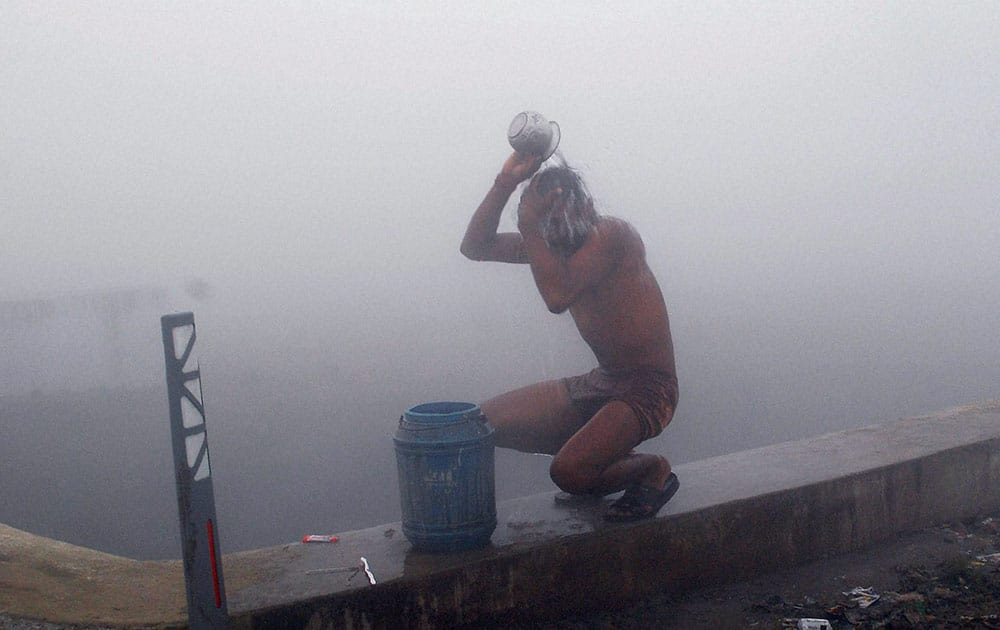 A youth bathing on a foggy morning in Allahabad.