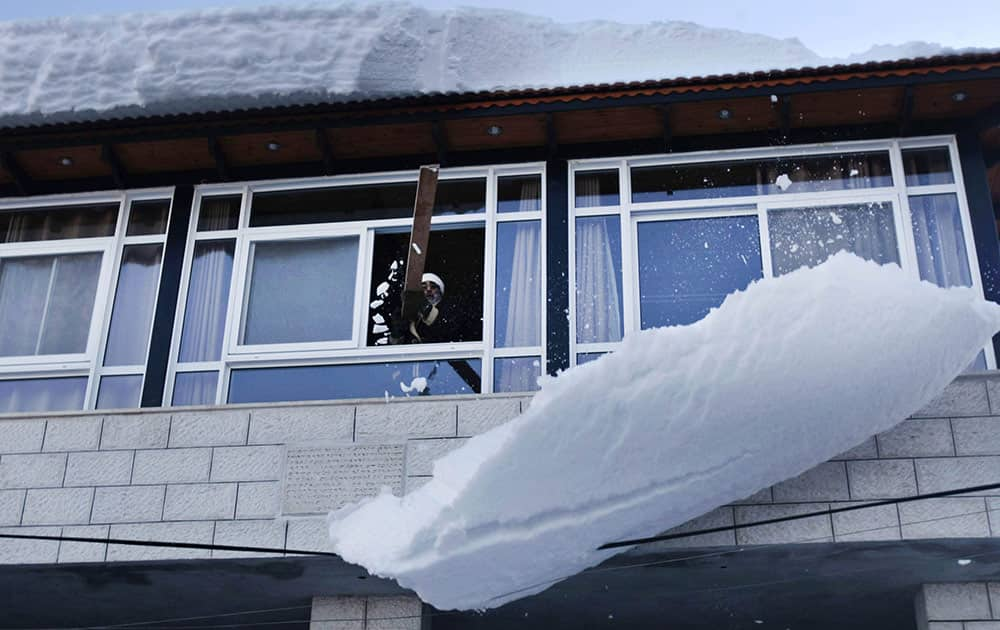 A Samaritan priest clears the snow on the roof of his house at Mount Gerzim near the West Bank town of Nablus.