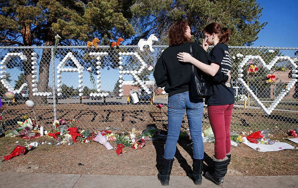 Arapahoe High School junior Emily Evans, right, and her mother Cristina hug while visiting a makeshift memorial bearing the name of wounded student Claire Davis, who was shot by a classmate during school three days earlier in an attack, in front of Arapahoe High School in Centennial, Colo.